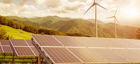 Row of solar panels against windmillss